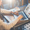 Graphics and diagrams on computer screen. Woman analyzing data. Student learning online. Freelancer working home. Young business woman sitting at table in coffee Stock Photo