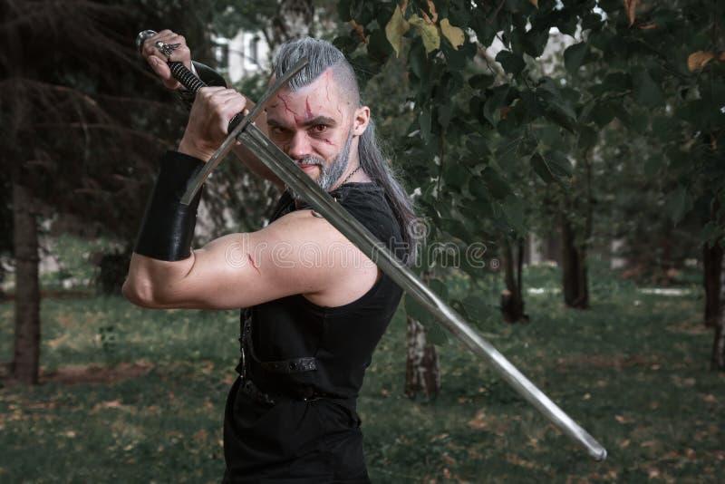  di Ñ osplay, vestito come un eroe Geralt di Rivia dal gioco il Witcher, un guerriero fantastico con una spada in sue mani immagini stock