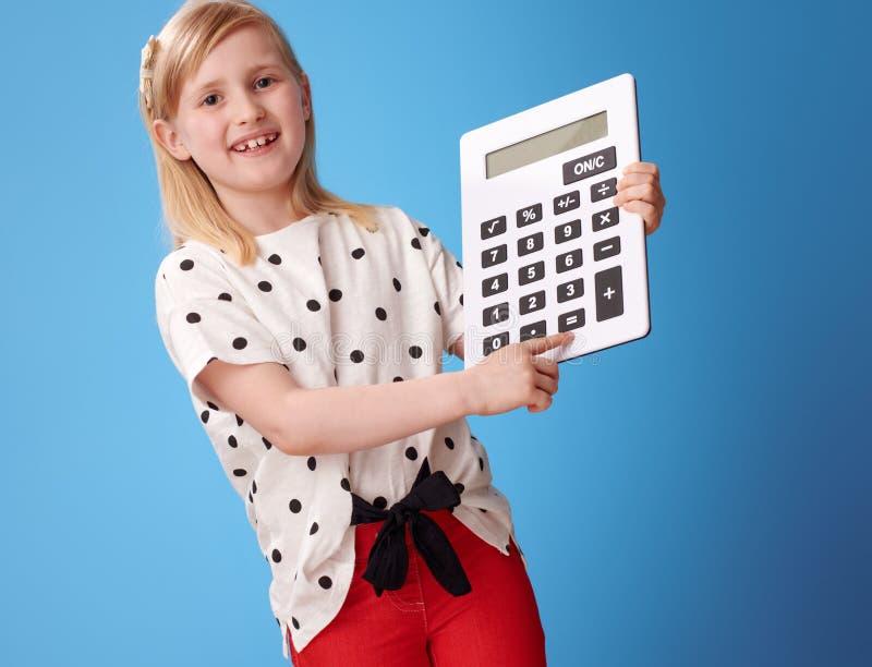  moderno feliz del niño Ñ que se lame en el botón en la calculadora en azul imagenes de archivo