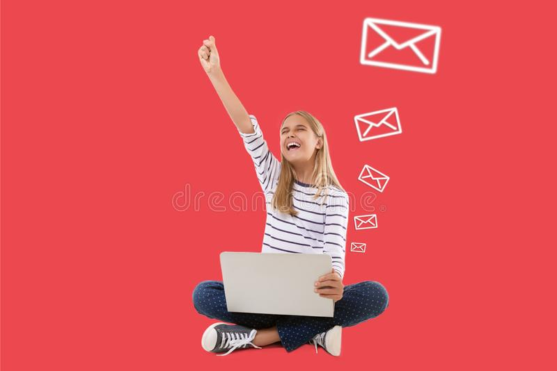 Excited teen girl with laptop celebrating success with one arm raised with emails icons over living coral background royalty free stock photos
