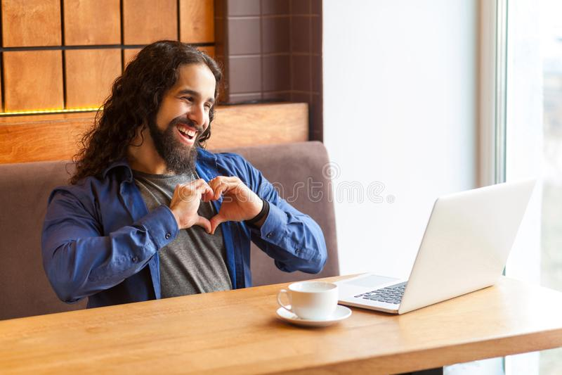 ¡Ámele! Retrato del freelancer adulto joven hermoso del hombre del romantik en el estilo sport que se sienta en café y que habla  foto de archivo