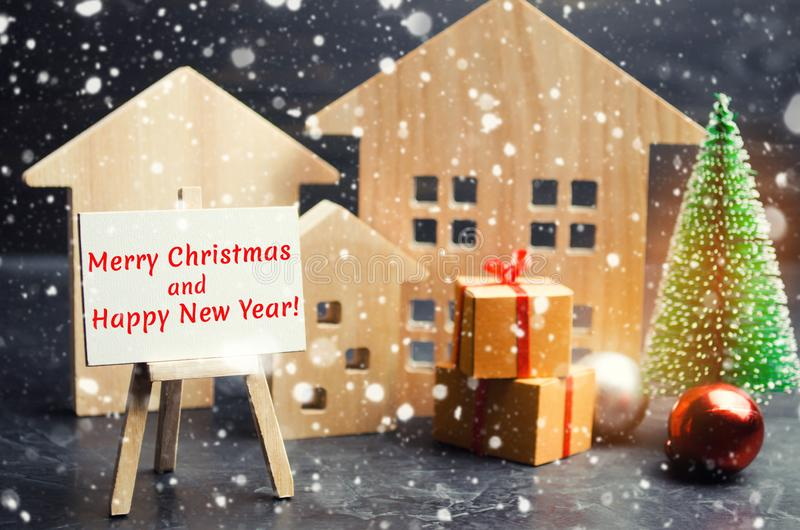 ¡Árbol de navidad, casas de madera y regalos con la Feliz Navidad de la inscripción 'y Feliz Año Nuevo! ' Invitación del Año Nuev imágenes de archivo libres de regalías