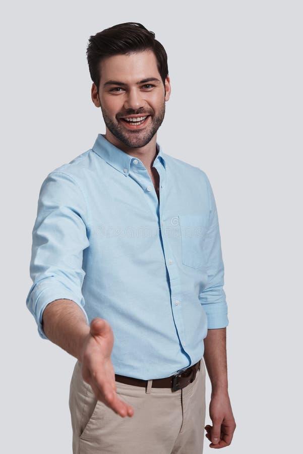 ¡ Bienvenido! Hombre joven apuesto que le saluda y que sonríe mientras que imagen de archivo libre de regalías