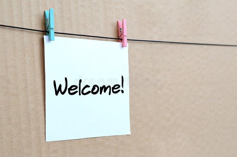 ¡ Bienvenido! La nota se escribe en una etiqueta engomada blanca que cuelgue con un cl imagenes de archivo