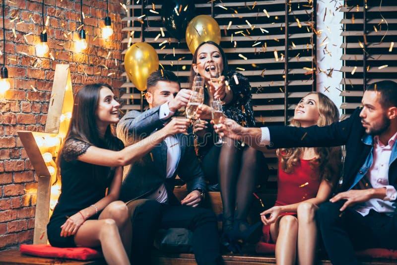 ¡Alegrías! Grupo de amigos que tintinean los vidrios de champán durante el PA imagenes de archivo