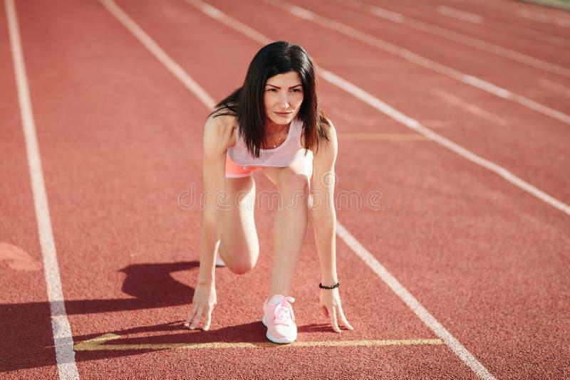 ¡Aliste para ir! Atleta de sexo femenino en pantalones cortos y camisetas sin mangas en la línea de salida de una pista del estad imagen de archivo