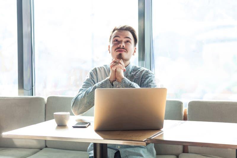 ¡Ayuda de dios yo o perdonar! Retrato del freelancer joven barbudo triste esperanzado en la camisa azul que se sienta en café y q imagenes de archivo