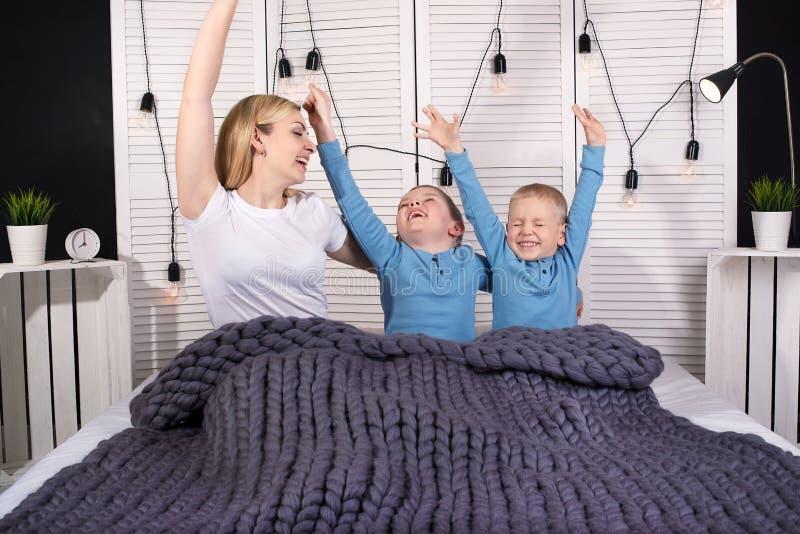 ¡Buenos días! La madre y dos hijos jovenes están estirando en cama El despertar positivo imagen de archivo