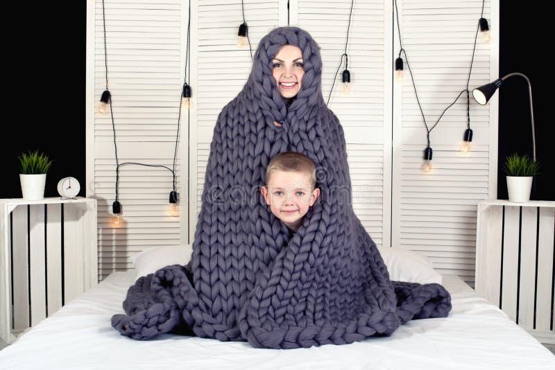 ¡Buenos días! Madre y pequeña piel del hijo debajo de una manta hecha punto El despertar positivo fotos de archivo libres de regalías