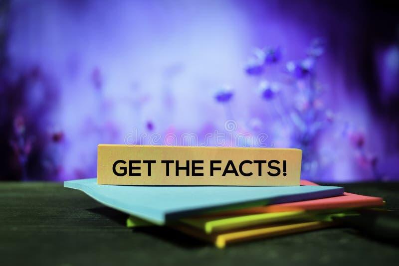 ¡Consiga los hechos! en las notas pegajosas con el fondo del bokeh imágenes de archivo libres de regalías