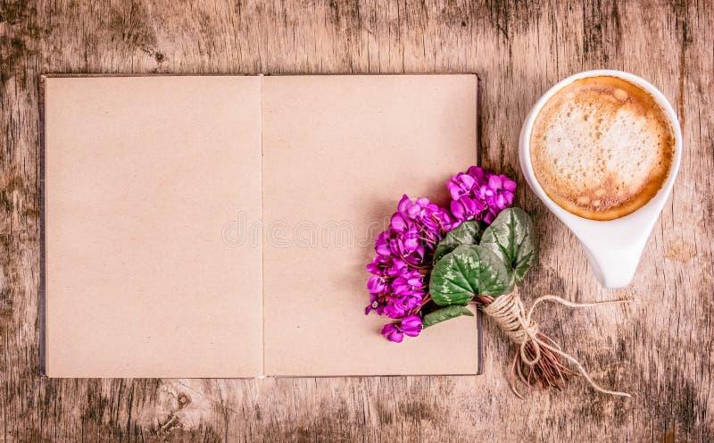 ¡De Ð para arriba del café, de flores y del libro Abra el libro, las violetas delicadas y la taza de café fragante fotografía de archivo libre de regalías
