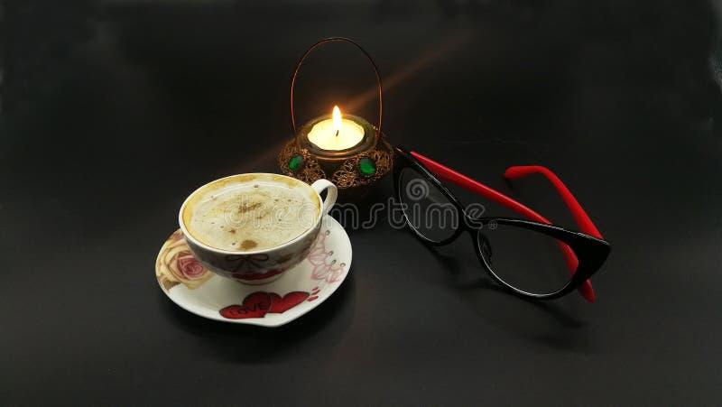 ¡De Ð para arriba del café Lentes negras y rojas femeninas Fondo oscuro negro Sauser con las flores y los corazones del amor Vela imagen de archivo