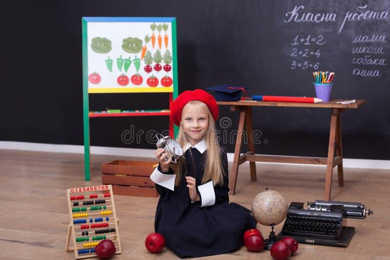 ¡De nuevo a escuela! La colegiala se sienta en una lección con un reloj en sus manos Concepto de la escuela En la pizarra en la l foto de archivo libre de regalías