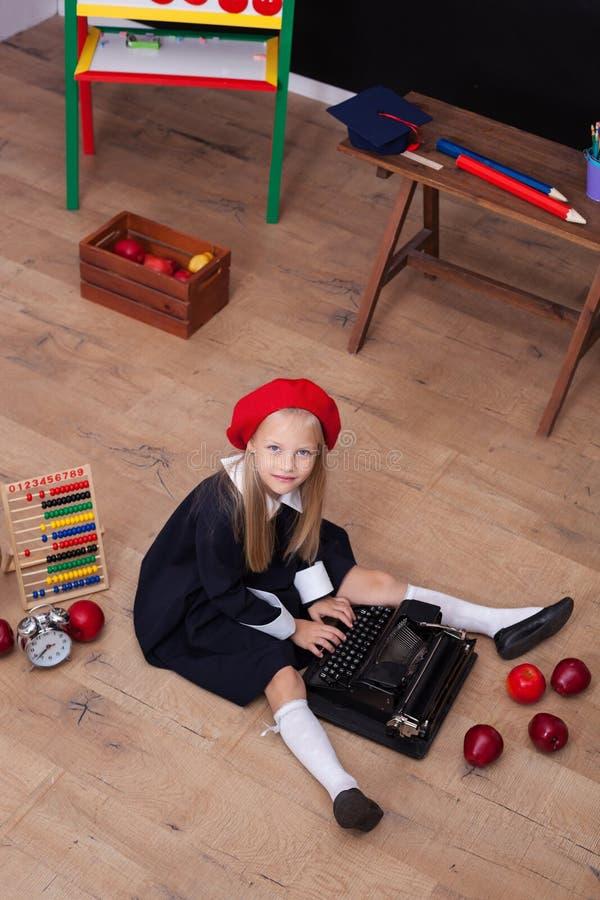 ¡De nuevo a escuela! La muchacha en la boina se sienta con una máquina de escribir y aprende en clase En la pizarra en la lengua  fotografía de archivo