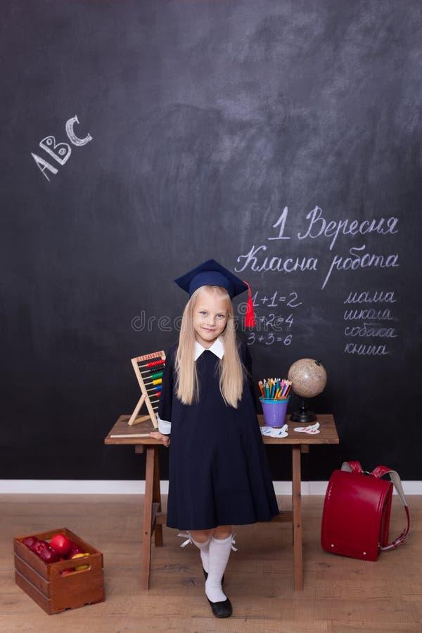 ¡De nuevo a escuela! La niña alegre en la escuela se está colocando cerca del escritorio Mirada en la c?mara Concepto de la escue foto de archivo libre de regalías