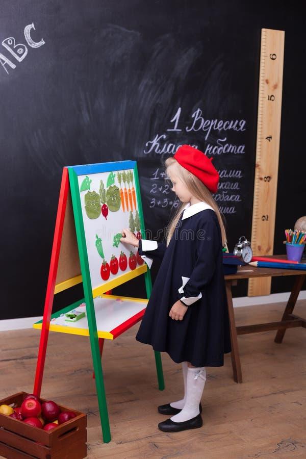 ¡De nuevo a escuela! La niña alegre se está colocando cerca del consejo escolar Concepto de la escuela Respuestas de la colegiala fotos de archivo libres de regalías