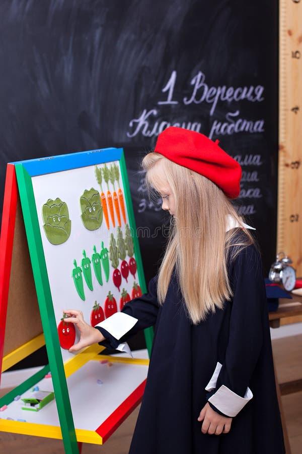 ¡De nuevo a escuela! la niña se está colocando cerca del consejo escolar En la pizarra en ucraniano se escribe el ?1 de septiembr fotografía de archivo libre de regalías