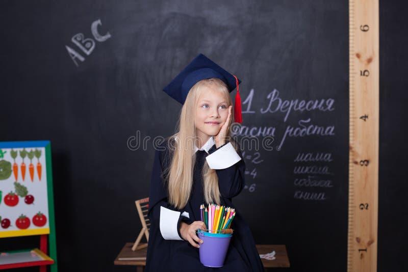 ¡De nuevo a escuela! Muchacha alegre en la escuela con los lápices cerca de la pizarra Concepto de la escuela En la pizarra en el fotografía de archivo