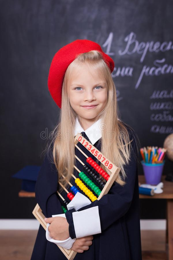 ¡De nuevo a escuela! Soportes alegres de la niña con las cuentas Concepto de la escuela Respuestas de la colegiala en la lección  imagen de archivo