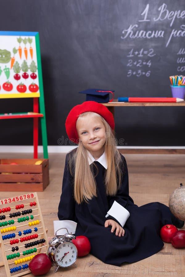 ¡De nuevo a escuela! Una muchacha en el uniforme escolar que se sienta en una lección Responde a la lección En la pizarra en la l imagenes de archivo