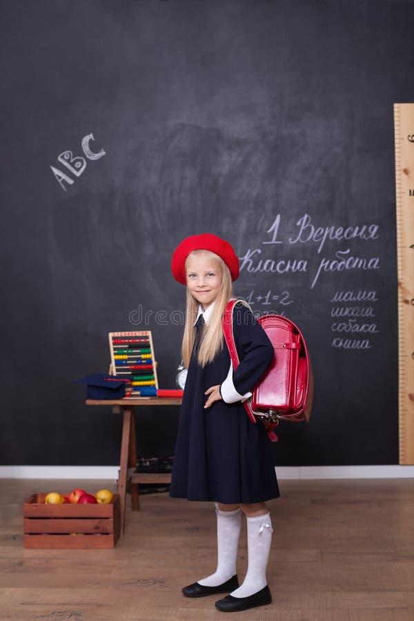 ¡De nuevo a escuela! Una muchacha se coloca en escuela con una mochila roja Responde a la lecci?n Concepto de la escuela En la pi fotos de archivo
