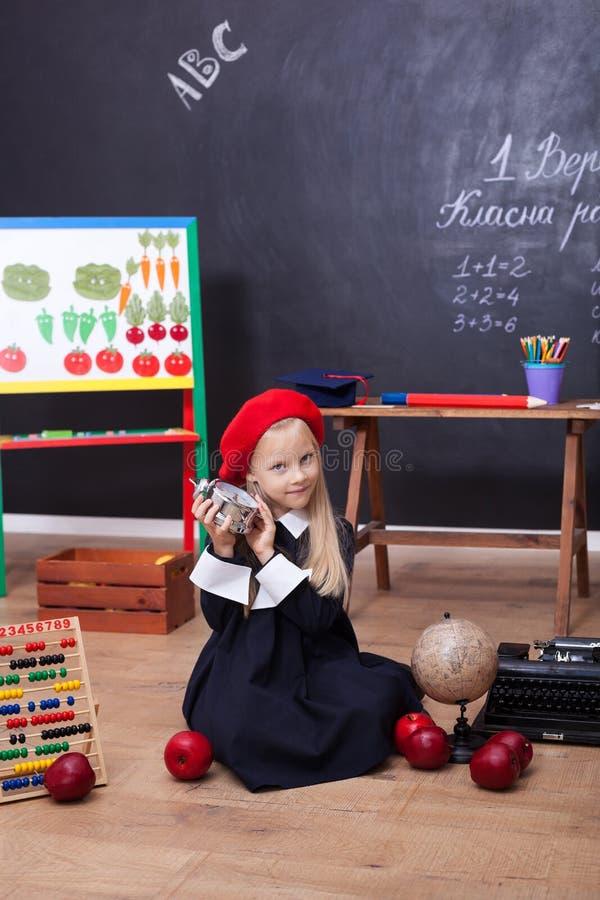 ¡De nuevo a escuela! Una niña se sienta en una lección con un reloj en sus manos La colegiala responde a la lecci?n El niño está  imágenes de archivo libres de regalías