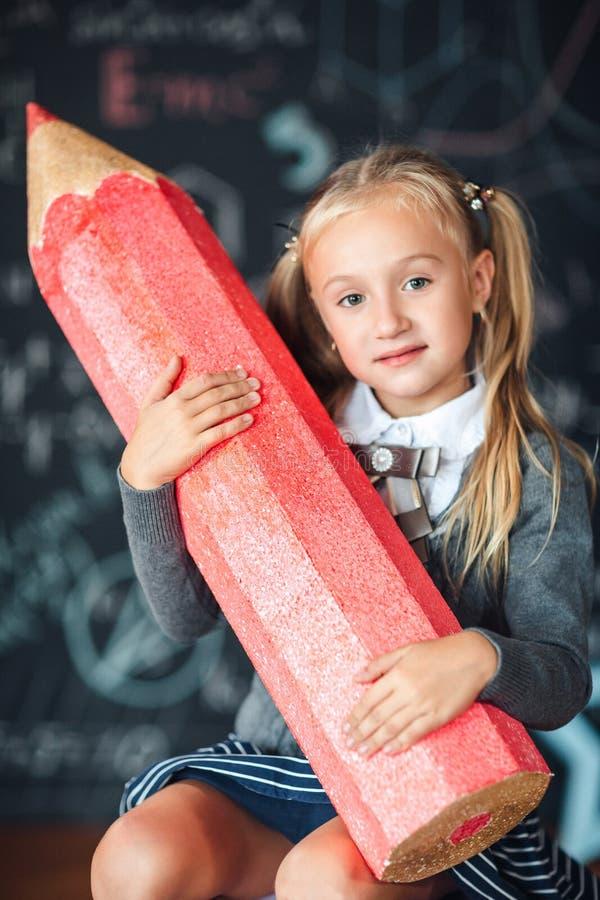 ¡De nuevo a escuela! Una pequeña muchacha rubia feliz en uniforme escolar se sienta con el lápiz rojo muy grande en sus manos en  imagen de archivo