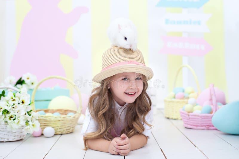 ¡El concepto de Pascua, de días de fiesta y de gente! La niña lleva a cabo el conejito de pascua en su cabeza y juegos con ella M imagenes de archivo