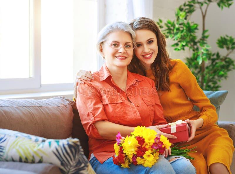 ¡El día de madre feliz! la hija adulta da las flores y felicita a una madre mayor el día de fiesta fotos de archivo
