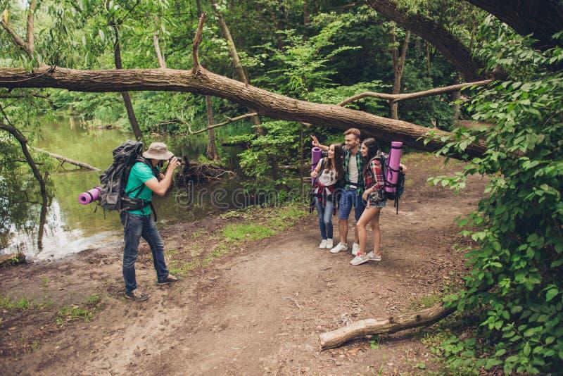 ¡El fotógrafo de sexo masculino está tomando la foto de sus tres amigos cerca del lago en la madera de la primavera, naturaleza t imagen de archivo libre de regalías