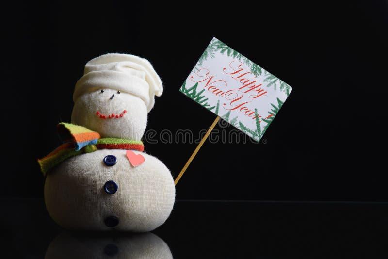 """¡El muñeco de nieve, tablero del cartel con el palillo atado, manda un SMS a Año Nuevo """"Happy!  del †fotos de archivo"""