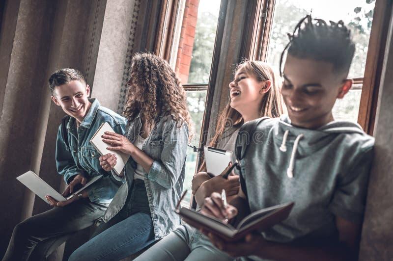 ¡Es historia de la diversión! Los estudiantes felices están charlando, rato sonriente tienen una rotura foto de archivo