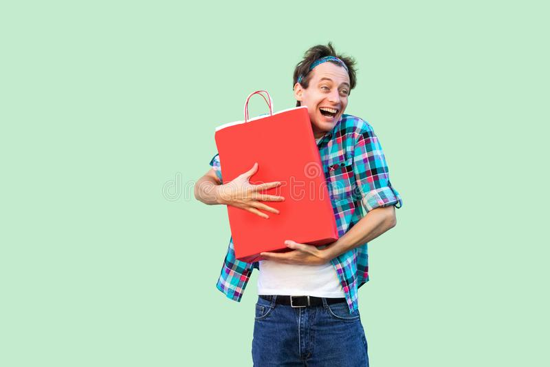 ¡Es mi! Hombre shopoholic adulto joven feliz loco en la camiseta blanca y la situación a cuadros de la camisa, abrazando bolsos d fotos de archivo libres de regalías