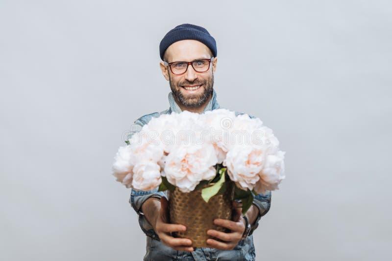 ¡Estas flores están para usted! El varón barbudo sonriente alegre estira las manos mientras que el manojo de los controles de flo foto de archivo