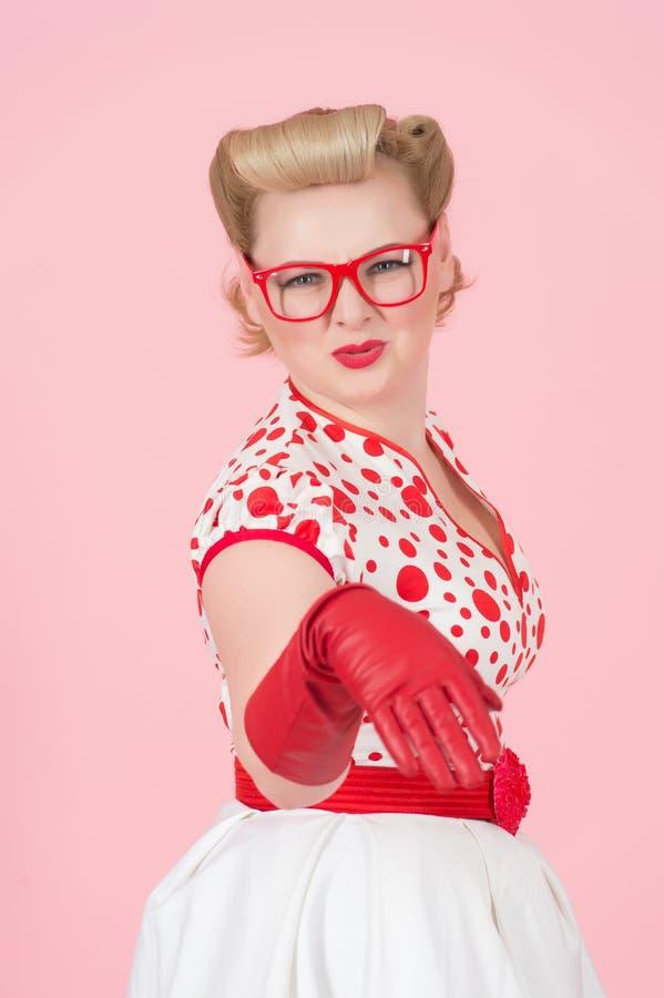 ¡Ey usted compinche! Mujer rubia joven chocada que señala a mano en guantes rojos en la cámara y la boca abierta Estudio tirado d fotos de archivo