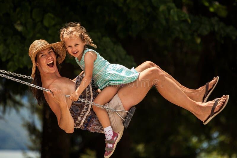 ¡Familia cariñosa feliz! Madre joven y su hija del niño que balancean en los oscilaciones y que ríen una tarde del verano al aire fotos de archivo