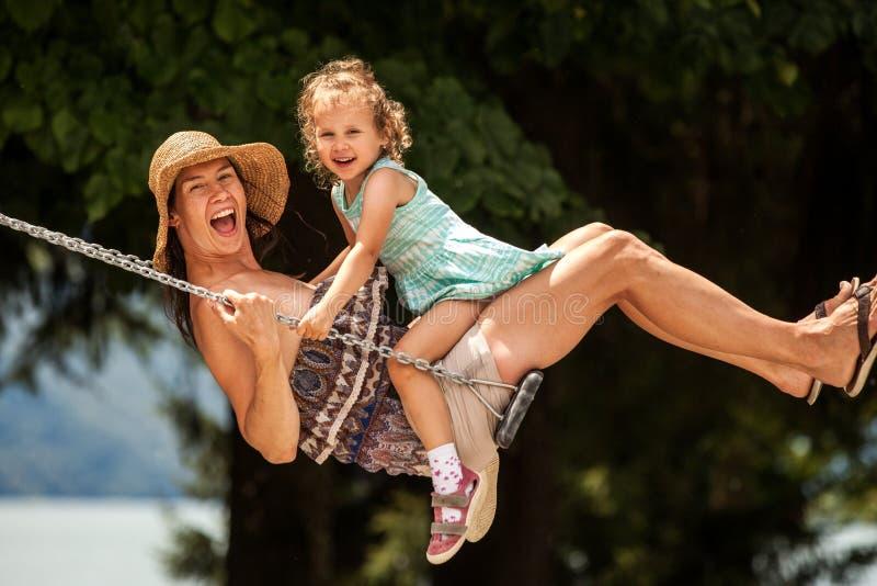 ¡Familia cariñosa feliz! Madre joven y su hija del niño que balancean en los oscilaciones y que ríen una tarde del verano al aire imagenes de archivo