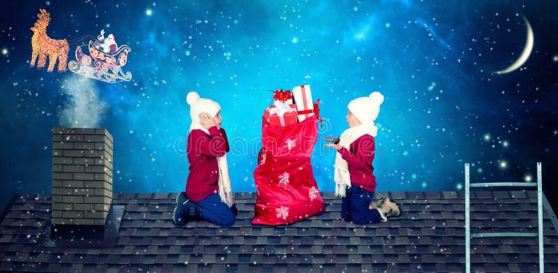 ¡Feliz Navidad y buenas fiestas! Los niños abren un bolso de regalos de Papá Noel Papá Noel cayó un saco de presentes a los peque imagenes de archivo