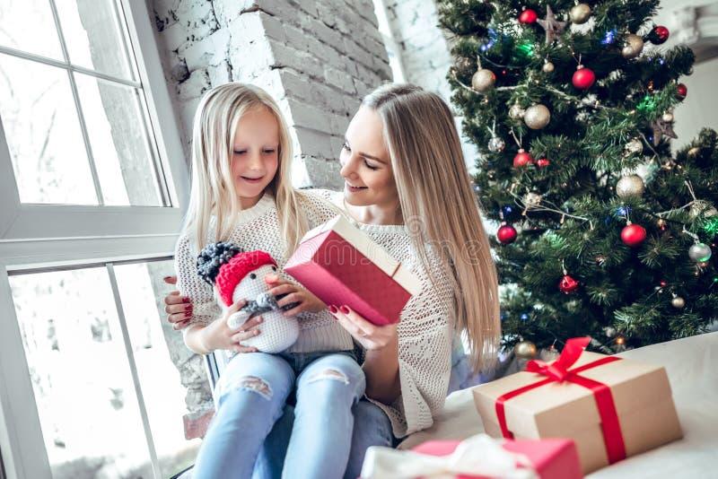 ¡Feliz Navidad y buenas fiestas! Mamá alegre y su muchacha linda de la hija que intercambian los regalos fotografía de archivo libre de regalías