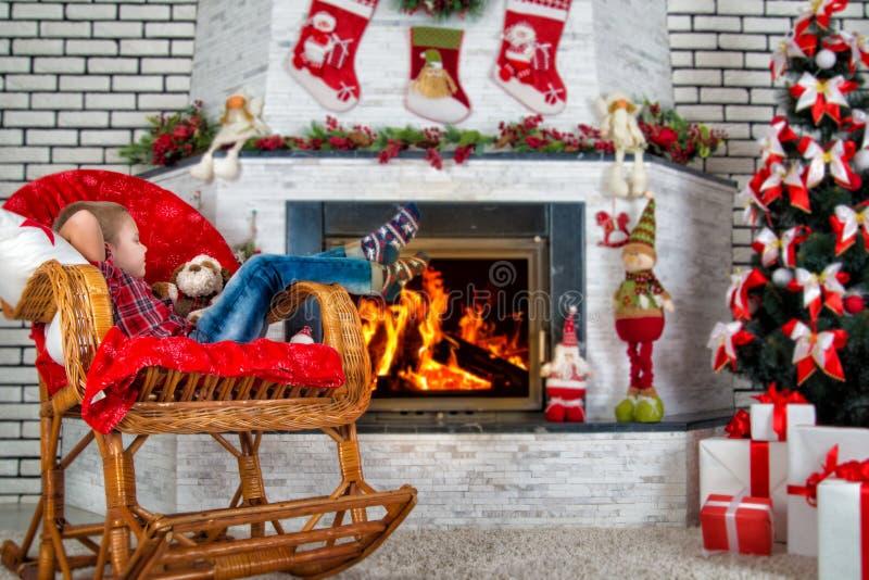 ¡Feliz Navidad y buenas fiestas! Muchacho del niño que se sienta cerca del árbol de navidad y de la chimenea adornados en mecedor foto de archivo libre de regalías