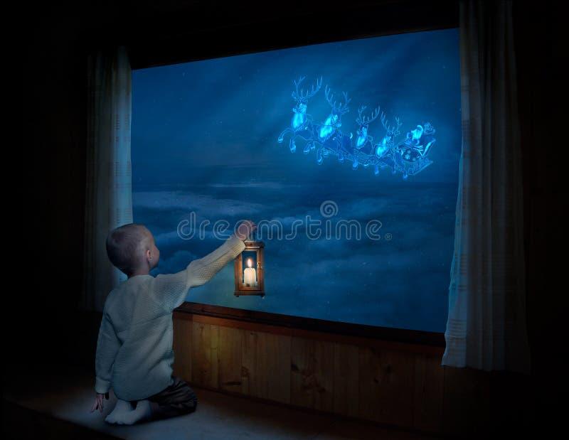 ¡Feliz Navidad y buenas fiestas! Niño pequeño que se sienta en la ventana y que mira el vuelo de Santa Claus en su trineo contra  imagen de archivo