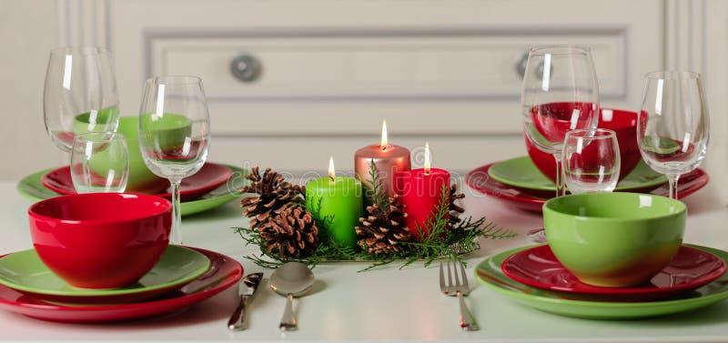 ¡Feliz Navidad y Feliz Año Nuevo! Тable que fija la decoración festiva - platos, velas y conos de abeto verdes y rojos Decoració imagen de archivo libre de regalías