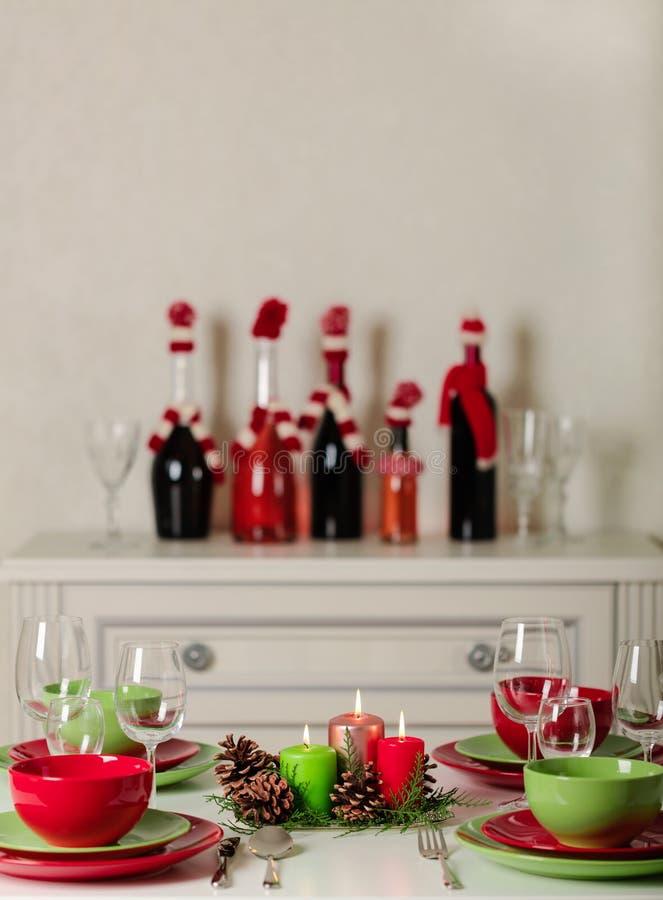 ¡Feliz Navidad y Feliz Año Nuevo! Тable que fija la decoración festiva - platos, velas y conos de abeto verdes y rojos Decoració fotos de archivo libres de regalías