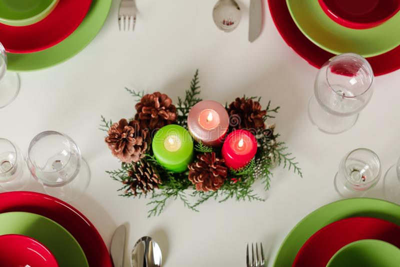 ¡Feliz Navidad y Feliz Año Nuevo! Тable que fija la decoración festiva - platos, velas y conos de abeto verdes y rojos Decoració imagenes de archivo