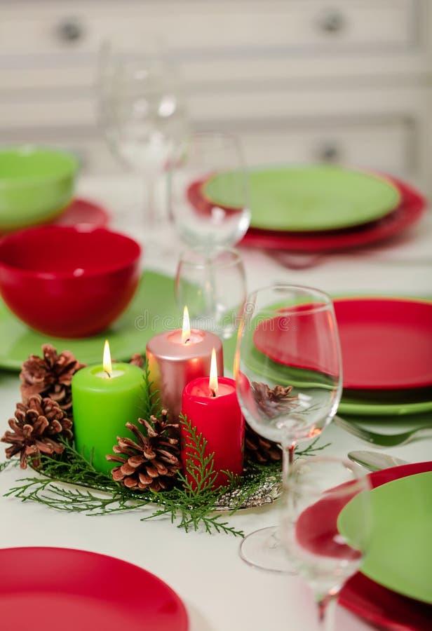 ¡Feliz Navidad y Feliz Año Nuevo! Тable que fija la decoración festiva - platos, velas y conos de abeto verdes y rojos Decoració imagen de archivo