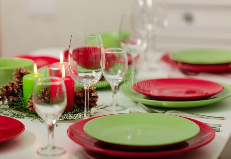 ¡Feliz Navidad y Feliz Año Nuevo! Тable que fija la decoración festiva - platos, velas y conos de abeto verdes y rojos Decoració fotografía de archivo