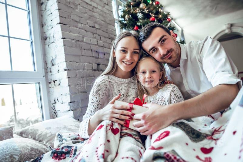 ¡Feliz Navidad y Feliz Año Nuevo! Familia feliz con la caja de regalo que se sienta en cama en casa cerca del árbol de navidad imagenes de archivo