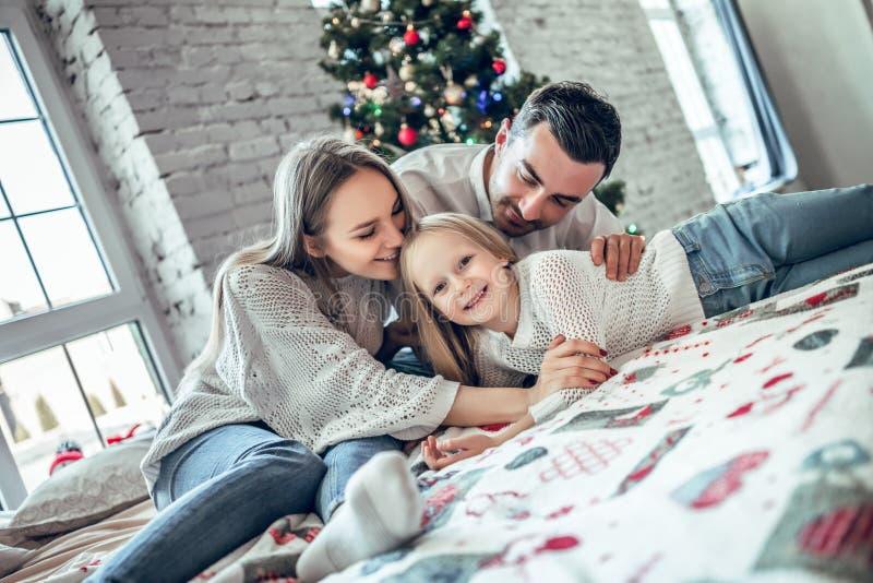 ¡Feliz Navidad y Feliz Año Nuevo! La familia feliz está mintiendo en cama cerca del árbol de navidad hermoso fotografía de archivo