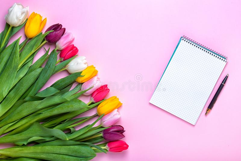 ¡Fondo de la primavera! Tulipanes coloridos de un ramo y un cuaderno vacío para las entradas románticas fotografía de archivo