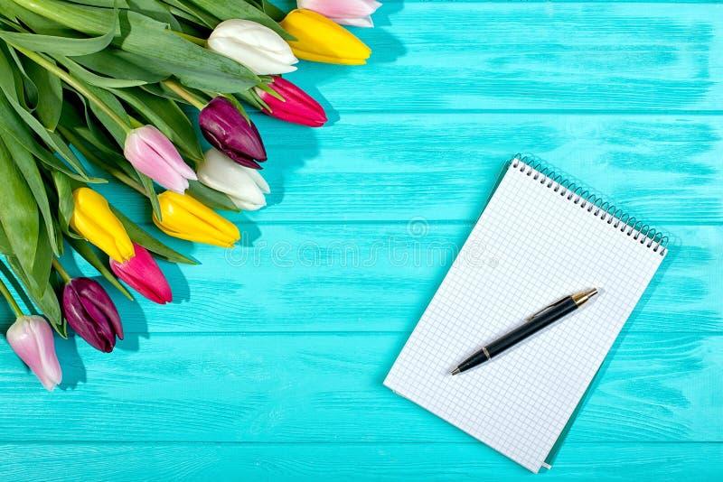 ¡Fondo de la primavera! Tulipanes coloridos de un ramo y un cuaderno vacío para las entradas románticas foto de archivo